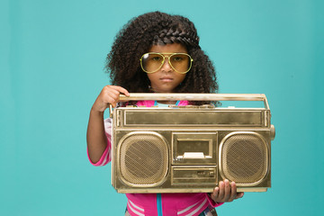 Girl wearing sunglasses and holding gold boombox