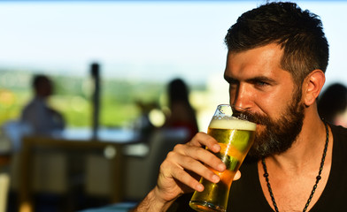 Bearded man drinking lager beer. Senior man drinking beer with surprise face. Man holds glass of...