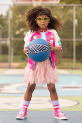 Young girl poses on playground with basketball and tutu