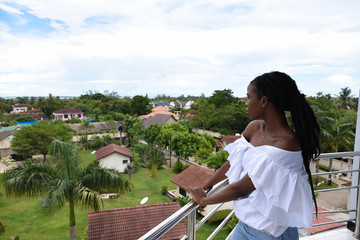 Woman looks out over buildings in tropical landscape