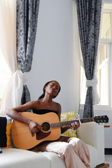 Young woman plays guitar while sitting on sofa