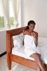 Young woman in towel looks at mobile phone