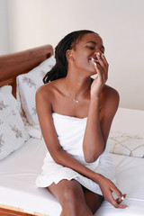 Laughing young woman sits on bed in towel
