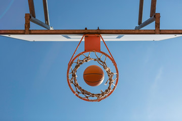 Basketball and hoop, blue sky, upward view