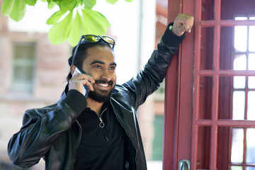 Portrait of smiling young man on the phone outdoors