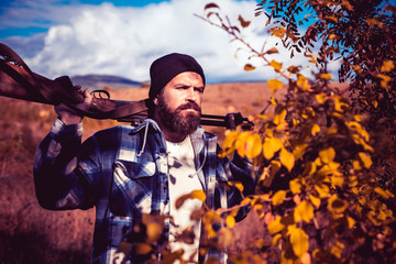 Hunter with shotgun gun on hunt. Autumn hunting season. Autunm hunting. Hunting Licenses. Bearded hunter man holding gun and walking in forest.