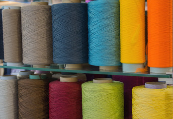 Bobbins with multicolored threads for sewing. Fabric and textile industry Fototapete