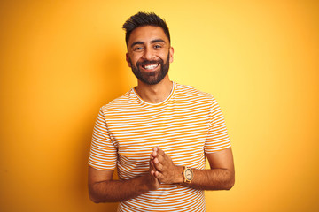 Young indian man wearing t-shirt standing over isolated yellow background Hands together and fingers crossed smiling relaxed and cheerful. Success and optimistic Wall mural