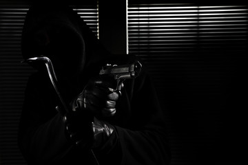 burglary and robbery. skillful professional masked burglar holding a gun and crowbar and breaking into the house, hand close up on black window background