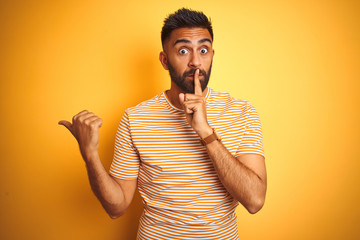 Young indian man wearing t-shirt standing over isolated yellow background asking to be quiet with finger on lips pointing with hand to the side. Silence and secret concept. Wall mural