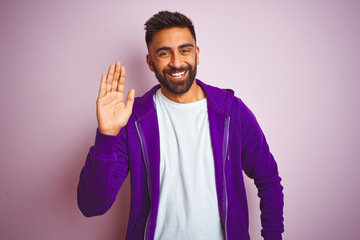 Young indian man wearing purple sweatshirt standing over isolated pink background Waiving saying hello happy and smiling, friendly welcome gesture Fototapete