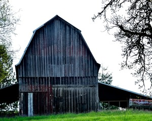 Old weathered wood barn on hilltop with grey and red patina