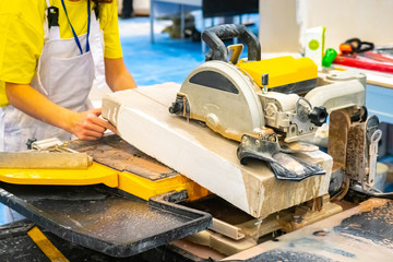 Shop with a circular saw. Man sawing stone. Equipment for cutting tile and stone. Stone processing technology. Work electric stone cutter. Tile cutting machine.