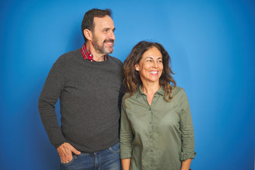 Beautiful middle age couple together standing over isolated blue background looking away to side with smile on face, natural expression. Laughing confident.