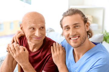 Elderly man with caregiver in nursing home Fototapete
