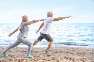Mature couple practicing yoga at sea resort Fototapete