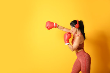 Sporty female boxer with headphones on color background