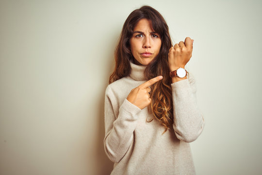 Young beautiful woman wearing winter sweater standing over white isolated background In hurry pointing to watch time, impatience, looking at the camera with relaxed expression