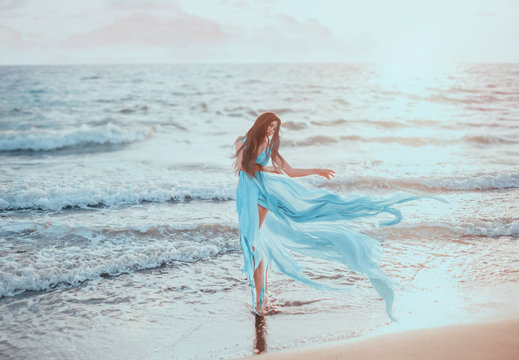 Young, slim woman with long legs dancing on the ocean