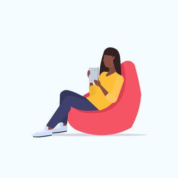 woman sitting in bean bag armchair african american girl freelancer or office worker using digital tablet social media communication concept flat full length