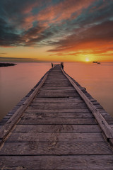Old wooden pier stretching out into the sea with a dramatic sunset.