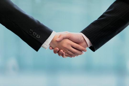 握手するビジネスマンとビジネスウーマンの手元