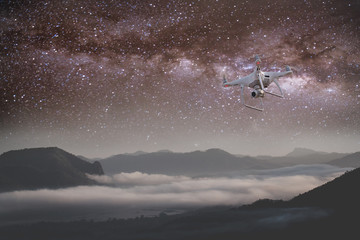 UAV Drone copter flying with digital camera.Drone with high resolution digital camera. Flying camera take a photo and video.The drone with professional camera takes pictures of the star galaxy .