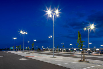 big modern empty parking lot with bright LED street lights at night Fotomurales