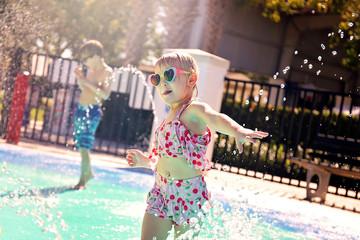 Toddler Child Running through Water Sprinklers at Outdoor Splash Park