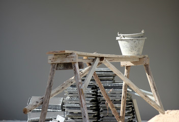 House construction details: An old bucket on a wooden stand against a dark grey wall background.