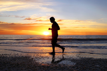 Silhouette of Peaceful Man Running Alone on Beach at Sunset