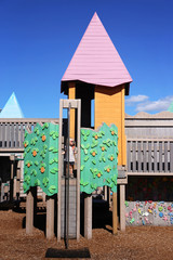 Little Kid Playing Inside Playground Castle on Sunny Summer Day