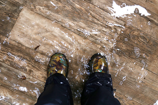 Woman's Feet Wearing Waterproof Boots, Standing in a Flooded House with Vinyl Wood Floors.