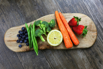 A Rainbow of Colorful, Healthy Fruits and Vegetables are Displayed on a Wooden Cutting Board