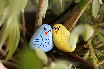 Handpainted Colorful Bird Kindness Rocks Sitting in a Green Plant