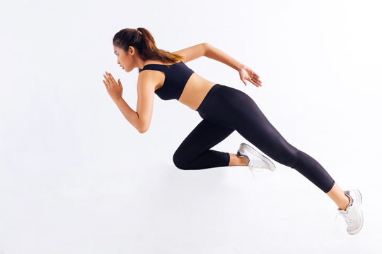 Side view of slim Asian female in black sportswear sprinting fast during workout against white background