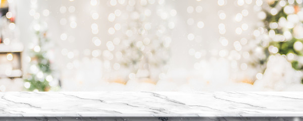 Christmas background of marble table top with abstract warm living room decor with christmas tree string light blur bokeh with snow,Holiday backdrop, panoramic Mock up banner for display of product.