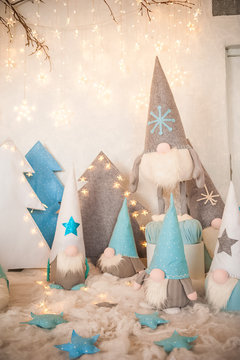 The concept of the New Year holidays. Many dwarfs with Christmas trees in a decorated Christmas room close-up and copy space.