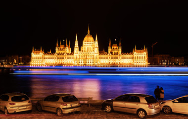Wall Mural - Hungarian parliament at night with couple looking at beautiful view in Budapest, Hungary