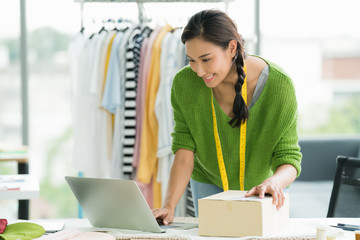 Young Asian woman entrepreneur / fashion designer working in studio and packing and sending product Fototapete