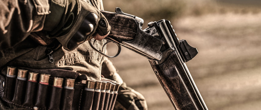 Hunter man. Hunting period. Male with a gun, rifle. Man is charging a hunting rifle. Male hunter in ready to hunt. Closeup. The man is on the hunt, sport