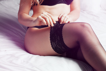 Cloeup portrait of a sexy female body in black lingerie and stockings in bed Wall mural