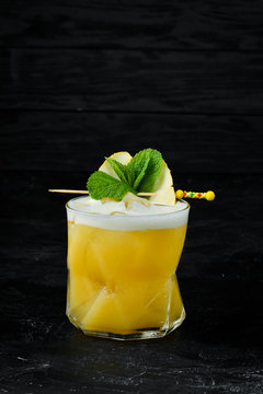 Yellow tropical drink cocktail in a glass. Passion fruit, lemon, rum.
