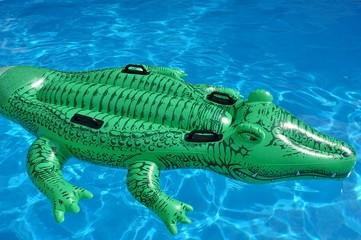 A green crocodile plastic pool float on a sandy beach