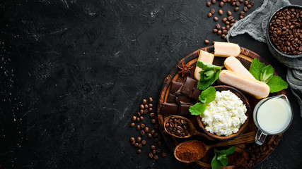 Tiramisu dessert. Ingredients for tiramisu preparation. Top view. On a black stone background. Free space for your text. Wall mural