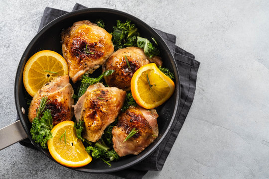 Chicken thighs with orange is a pan.