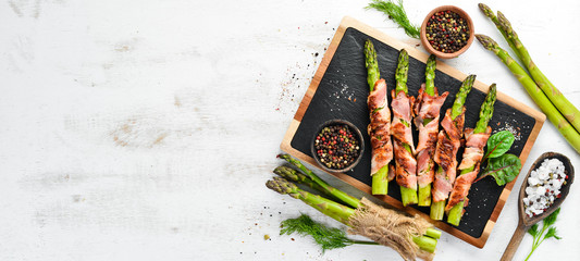 Fototapeta Asparagus baked with bacon and spices. Healthy food. Top view. Free space for your text.