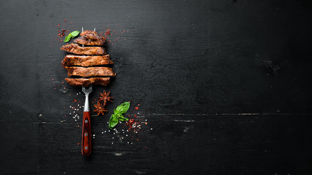 Pork steak on the fork. On a wooden background. Top view. Free space for your text.