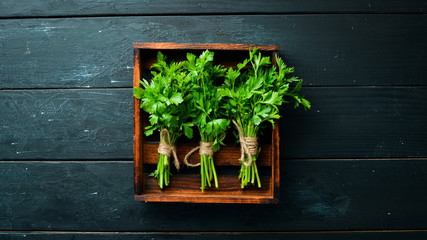 Wall Mural - Fresh parsley on a wooden background. Top view. Free space for your text.