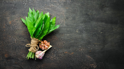 Wall Mural - Fresh wild garlic leaves on a wooden background. Top view. Free space for your text.